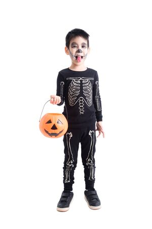 Little asian boy in skeleton costume for halloween celebration holding pumpkin bucket standing over white background 写真素材