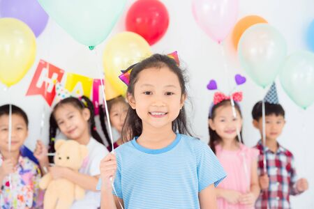 Little pretty girl holding green balloon and smiles in birthday party with friends