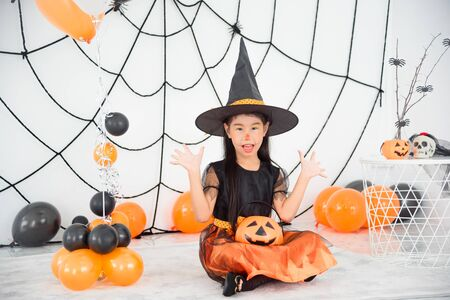 Pretty asian girl in witch costume sitting on the floor with pumpkin bucket in room with Halloween decoration 写真素材