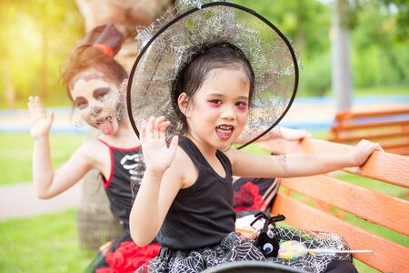 Little asian girls in halloween costume celebrate Halloween festival with friend in park. 写真素材