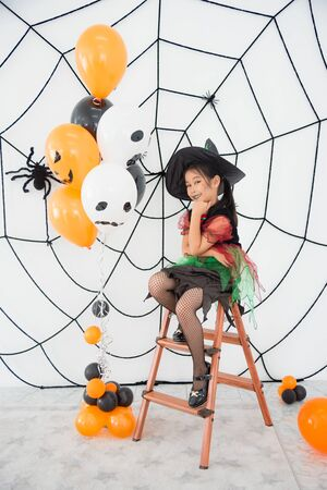Pretty asian girl in witch costume sitting in room with Halloween decoration and smile. 写真素材
