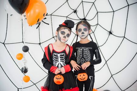 Two  asian girls in skeleton costume with makeup standing in room with Halloween decoration.
