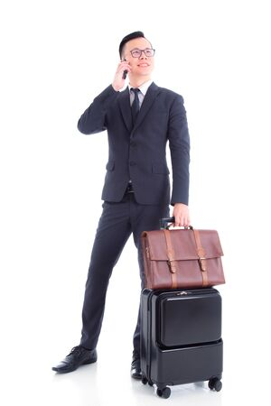Full length of handsome asian businessman wearing suit standing and smiling with baggage and calling via smart phone isolated over white background