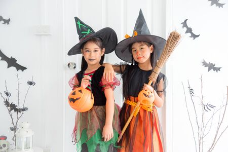 Two asian children in witch costume for celebrating Halloween festival standing in room with Halloween decoration.
