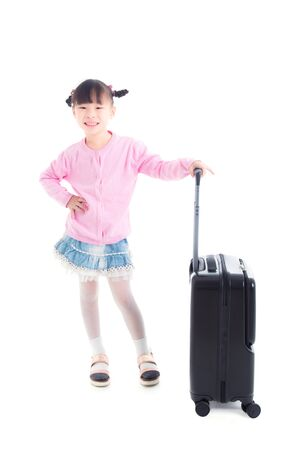 Little asian girl standing with wheel suitcase and smiles over white background 写真素材