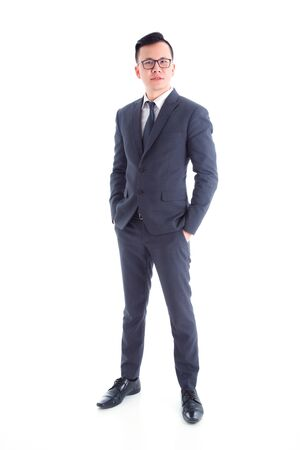 Full length of handsome asian businessman wearing suit standing and smiling isolated over white background
