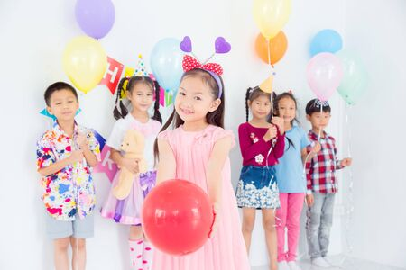 Little pretty girl holding red balloon and smiles in birthday party with friends 写真素材