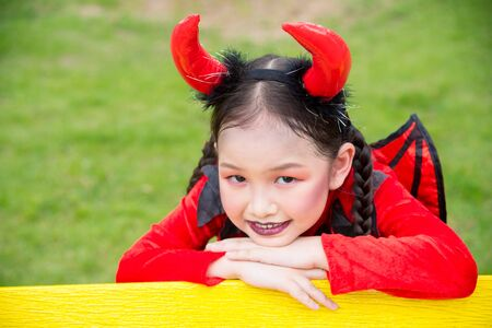 Little asian girl in devil costume celebrate Halloween outdoor.