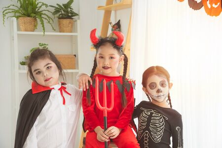 Group of little asian girls in Halloween costume standing and sitting together in room with Halloween decoration.