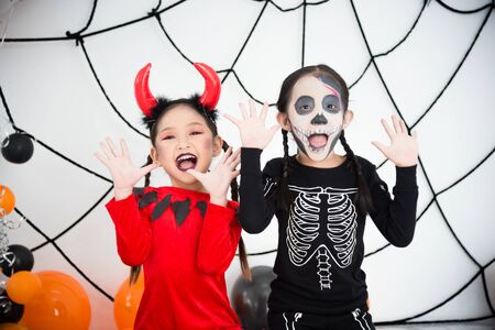 Two little asian girls in halloween costume smiling at camera.