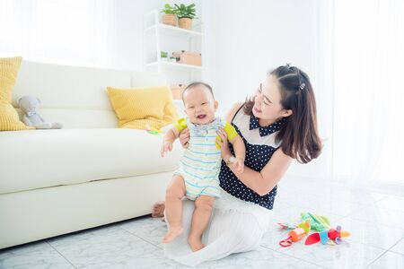 Little asian child smiles happily while playing with mother in living room