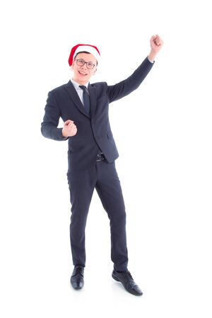 Full length of handsome asian businessman wearing suit and santa hat standing and smiling isolated over white background