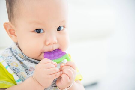 Little asian baby biting plastic teether and looking at camera Stockfoto