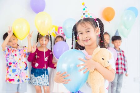 Little pretty girl holding blue balloon and smiles in birthday party with friends