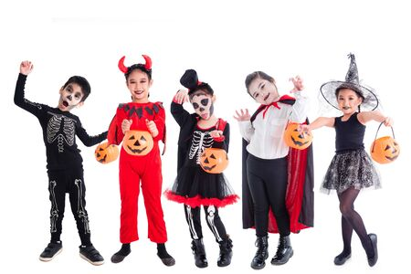 Group of asian children in halloween costume and makeup holding  pumpkin bucket standing over white background