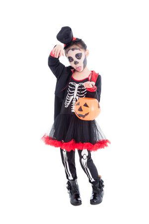 Full length of asian girl in skeleton costume holding halloween pumpkin bucket,standing over white background 写真素材
