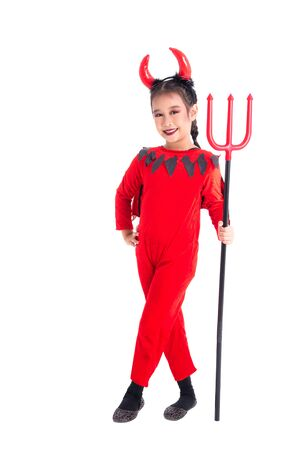 Full length of little asian girl in red devil costume standing and smiles over white background 写真素材