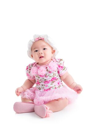 Full length of little asian baby girl in sweet pink dress sitting isolated over white background
