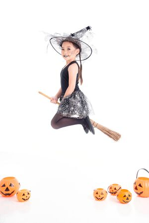 Little asian pretty girl in witch costume  flying on magic bloom over white background