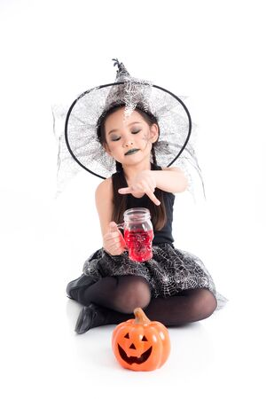 Full length of little asian girl in witch costume sitting and holding halloween glass drink over white background