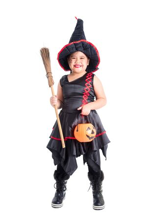 Full length of big asian girl in witch costume  standing and holding halloween pumpkin bucket over white background