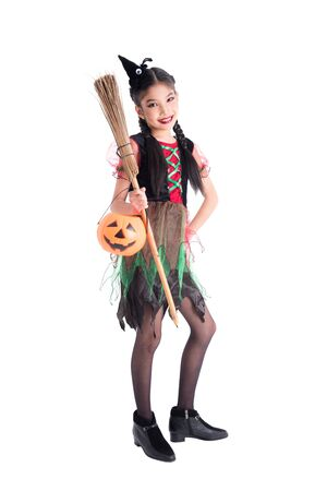 Full length of asian girl in witch costume holding bloom and halloween pumpkin bucket,standing with smile over white background