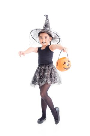 Full length of little asian girl in witch costume standing and holding halloween pumpkin bucket over white background