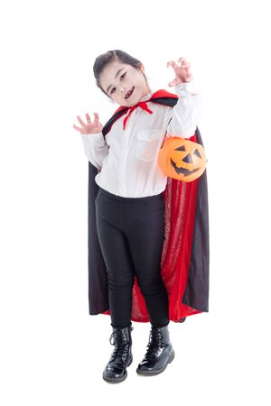 Full length of asian girl in vampire costume holding halloween pumpkin bucket and smiles over white background