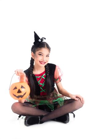 Full length of little asian girl in witch costume sitting and smiles with halloween pumpkin bucket over white background