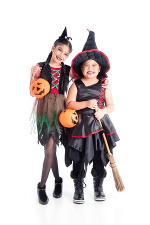 Full length of asian girls in witch costume  standing and holding halloween pumpkin bucket over white background 写真素材