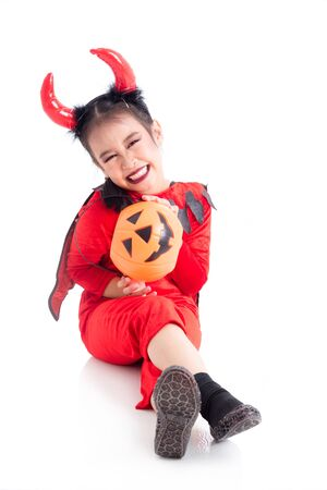 Full length of little asian girl in red devil costume sitting and smiles over white background