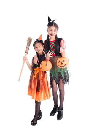 Full length of two asian girls in witch costume holding halloween pumpkin bucket and smile over white background