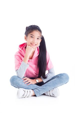 Full length of asian pretty girl sitting on the floor and smiles over white background 写真素材