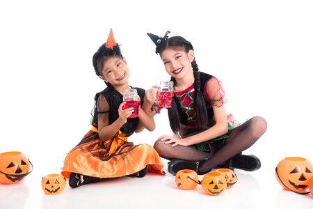 Full length of two asian girls in witch costume sitting on floor and  holding skull glass with red color drink and smile over white background