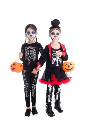Full length of two asian girls in skeleton costume holding halloween pumpkin bucket and smiles over white background