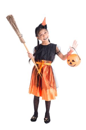 Full length of little asian girl in witch costume smiles with halloween pumpkin bucket over white background