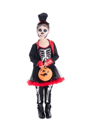 Full length of asian girl in skeleton costume holding halloween pumpkin bucket,standing and smiles over white background 写真素材