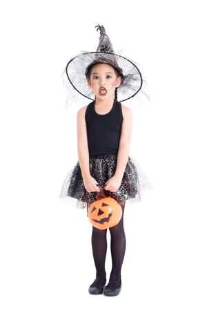 Full length of little asian pretty girl in witch costume  standing and holding halloween pumpkin bucket over white background 写真素材