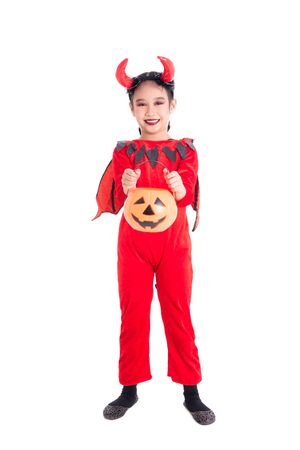 Full length of little asian girl in red devil costume standing and holding halloween pumpkin bucket over white background