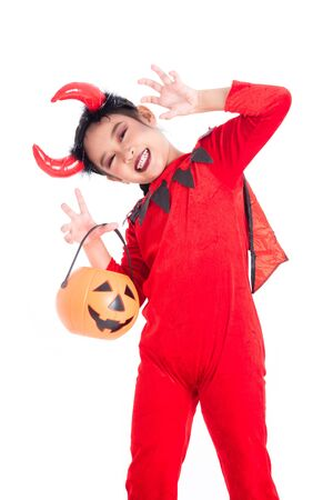 Little asian girl in red devil costume standing and holding halloween pumpkin bucket over white background