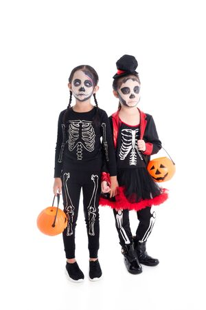 Full length of asian girls in skeleton costume holding halloween pumpkin bucket,standing over white background 写真素材