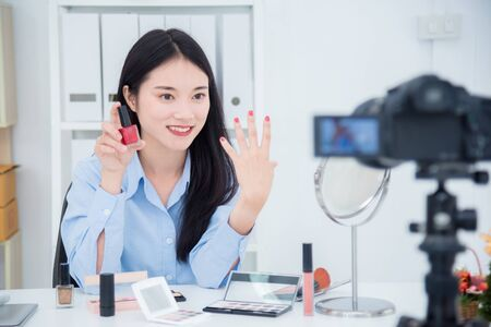 Beautiful asian girl talking about her nail polish color in front of camera to recording vlog video live streaming at her shop. Stock Photo