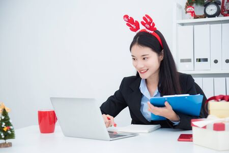 Happy asian businesswoman working with notebook computer on christmas holiday.
