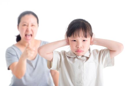 Displeased Girl covering her Ears from Scolded by her mother on white background