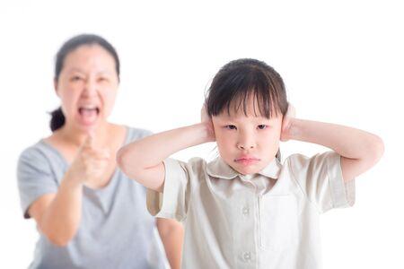 Fille mécontente couvrant ses oreilles de grondé par sa mère sur fond blanc Banque d'images