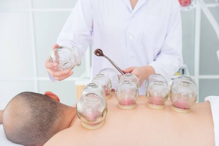 Close-up Of A Therapist Giving Cupping Treatment on patient back at alternative medical clinic.