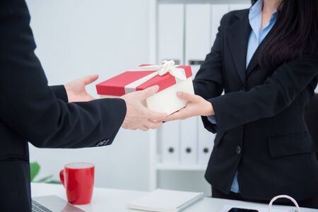 Hands of businesswoman giving christmas gift to her boss in office. Stock Photo