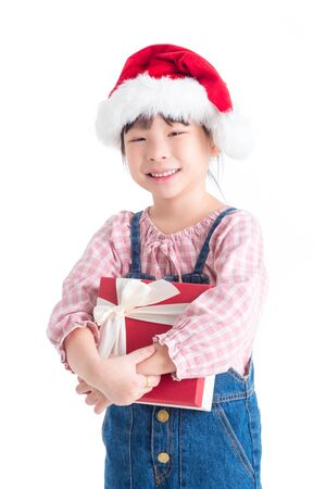 Little asian girl wearing santa claus hat holding gift box and smiles over white background