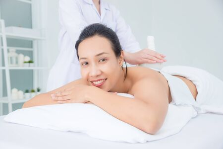 Beautiful asian woman smiling while therapist massaging by herbal ball at spa