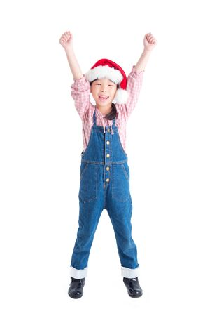 Full length of little asian girl wearing santa claus hat rising hands up and smiles over white background